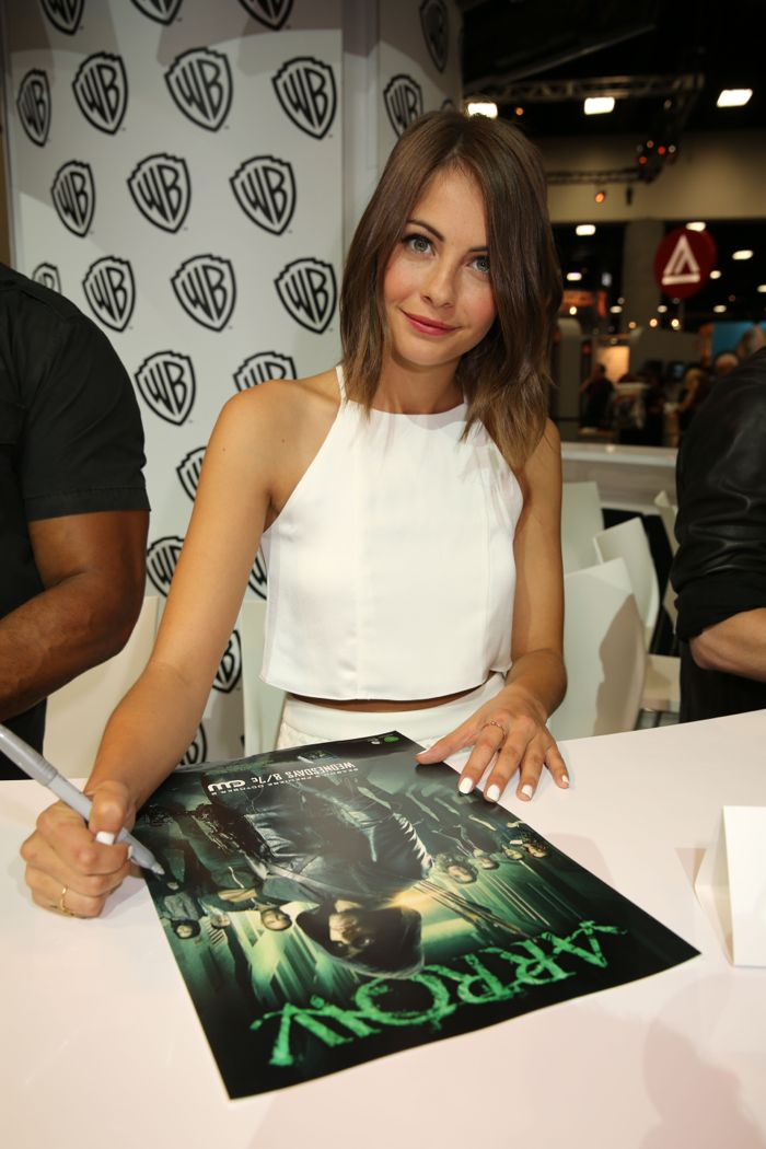 ARROW star Willa Holland signs the show's poster for a fan at the Warner Bros. booth at Comic-Con 2014