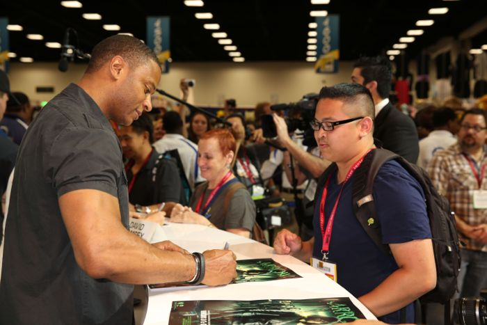 ARROW star David Ramsey signs for a fan at the Warner Bros. booth at Comic-Con 2014