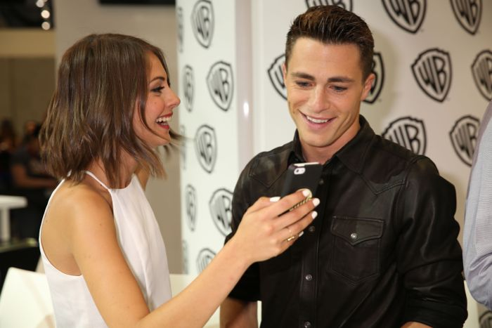 ARROW stars Willa Holland and Colton Haynes share a media moment at the Warner Bros. booth at Comic-Con 2014