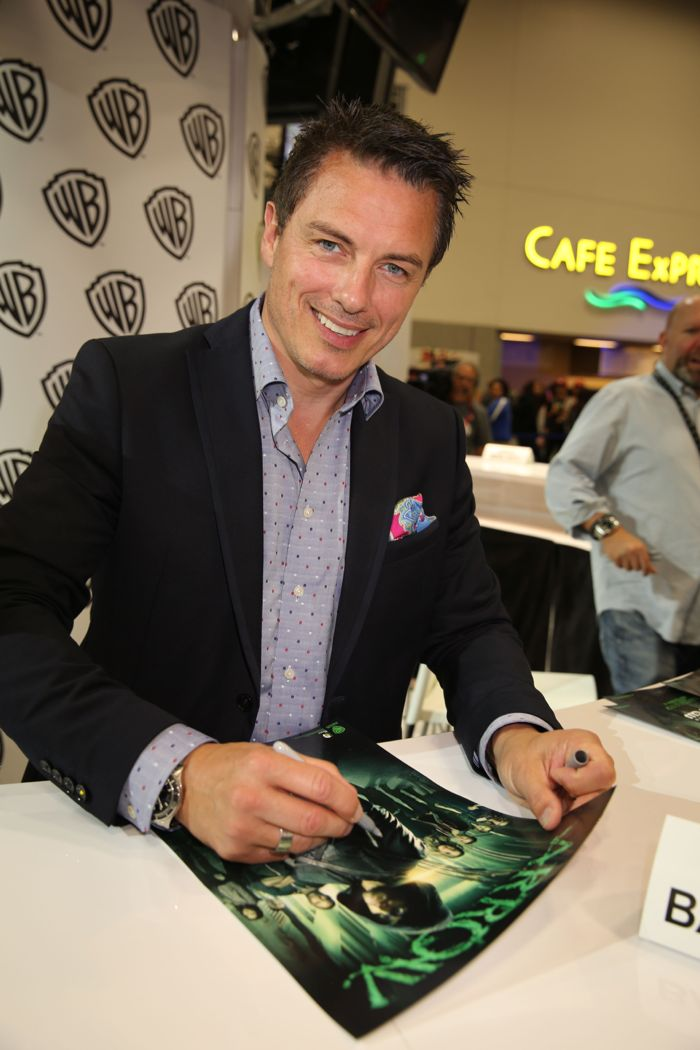 ARROW star John Barrowman signs for fans at the Warner Bros. booth at Comic-Con 2014