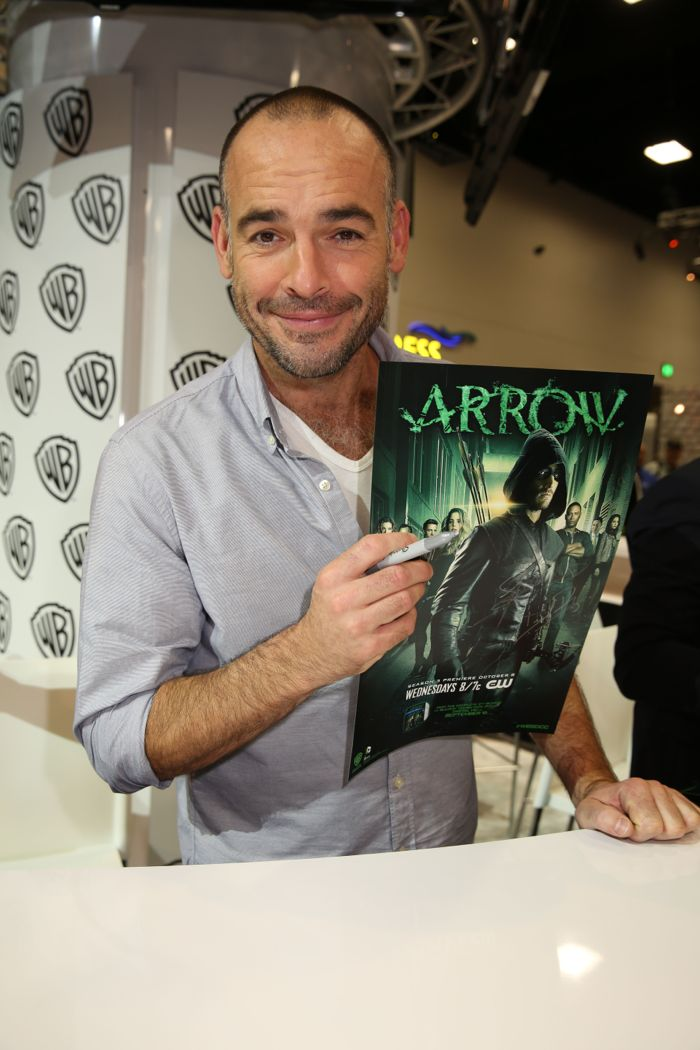 ARROW star Paul Blackthorne holds up the show's poster he is signing at the Warner Bros. booth at Comic-Con 2014