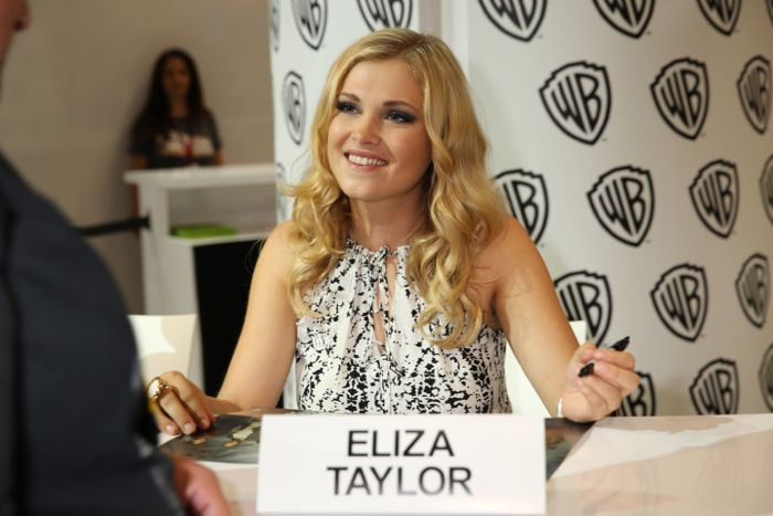 THE 100 star Eliza Taylor smiles and signs for fans at the Warner Bros. booth at Comic-Con 2014