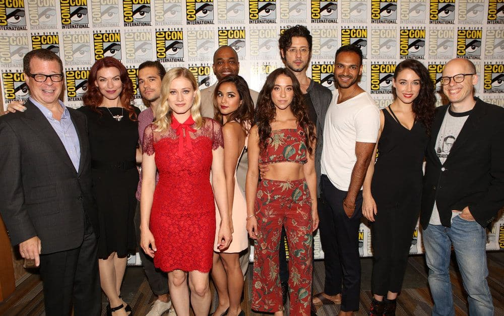 "COMIC-CON INTERNATIONAL: SAN DIEGO -- ""The Magicians Press Room"" -- Pictured: (l-r) Executive Producer John McNamara, Executive Producer/Writer Sera Gamble, Jason Ralph, Olivia Taylor Dudley, Summer Bishil, Rick Worthy, Stella Maeve, Hale Appleman, Arjun Gupta, Jade Tailor, Author Lev Grossman -- (Photo by: Evans Vestal Ward/Syfy)"