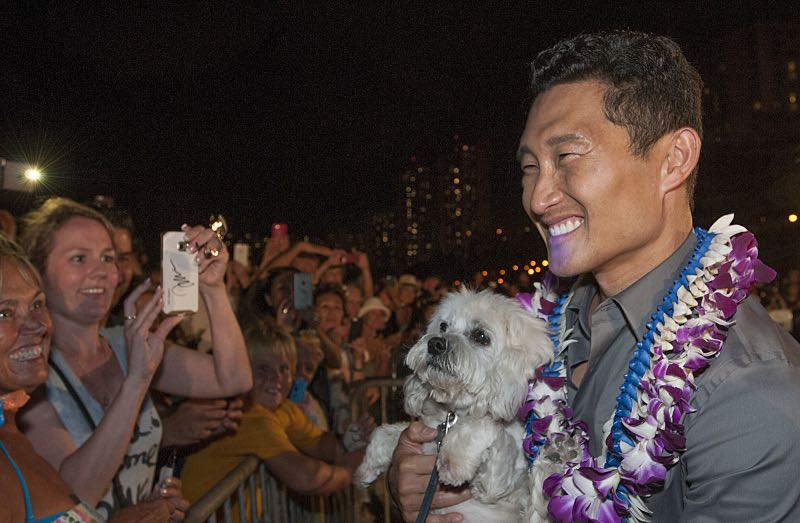 """Daniel Dae Kim who plays the part of """"Chin Ho Kelly"""" cuddles a fan's puppy on the red carpet at the seventh annual Sunset on the Beach event, where thousands of Oahu residents and visitors gathered in Waikiki to watch the season seven premiere of Hawaii Five-0, titled Makaukau 'oe e pa 'ani, on Friday, Sept. 23, 2016, in Honolulu. Photo: Norman Shapiro/CBS © 2016 CBS Broadcasting, Inc. All Rights Reserved"""