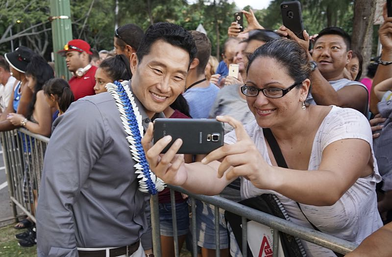 """Daniel Dae Kim who plays the part of """"Chin Ho Kelly"""" poses for a selfie with a fan on the red carpet at the seventh annual Sunset on the Beach event, where thousands of Oahu residents and visitors gathered in Waikiki to watch the season seven premiere of Hawaii Five-0, titled Makaukau 'oe e pa 'ani, on Friday, Sept. 23, 2016, in Honolulu. Photo: Hugh Gentry/CBS © 2016 CBS Broadcasting, Inc. All Rights Reserved"""