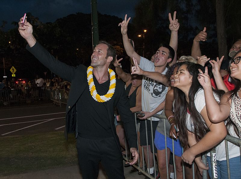 """Alex O'Loughlin who plays the part of """"Steve McGarrett"""" takes a selfie with the fans on the red carpet at the seventh annual Sunset on the Beach event, where thousands of Oahu residents and visitors gathered in Waikiki to watch the season seven premiere of Hawaii Five-0, titled Makaukau 'oe e pa 'ani, on Friday, Sept. 23, 2016, in Honolulu. Photo: Norman Shapiro/CBS © 2016 CBS Broadcasting, Inc. All Rights Reserved"""
