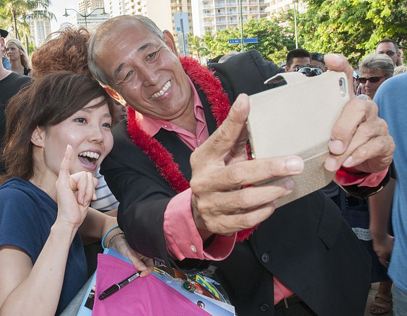 """Dennis Chun who plays the character """"Sgt. Duke Lukela"""" poses for a selfie picture with a fan on the red carpet at the seventh annual Sunset on the Beach event, where thousands of Oahu residents and visitors gathered in Waikiki to watch the season seven premiere of Hawaii Five-0, titled Makaukau 'oe e pa 'ani, on Friday, Sept. 23, 2016, in Honolulu. Photo: Norman Shapiro/CBS © 2016 CBS Broadcasting, Inc. All Rights Reserved"""
