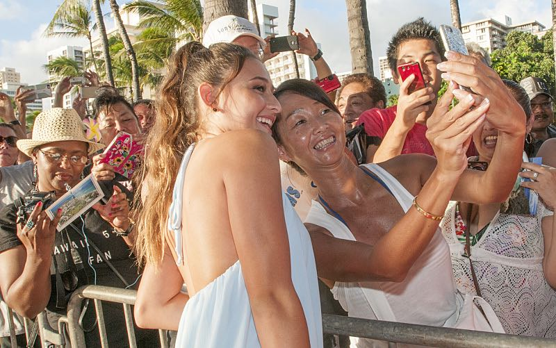 """Tailor Grubbs who plays the character """"Grace Williams"""" poses for a selfie picture with a fan on the red carpet at the seventh annual Sunset on the Beach event, where thousands of Oahu residents and visitors gathered in Waikiki to watch the season seven premiere of Hawaii Five-0, titled Makaukau 'oe e pa 'ani, on Friday, Sept. 23, 2016, in Honolulu. Photo: Norman Shapiro/CBS © 2016 CBS Broadcasting, Inc. All Rights Reserved"""