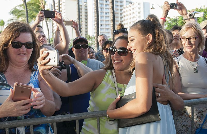 """Teilor Grubbs who plays the character """"Grace Williams"""" poses for a selfie picture with a fan on the red carpet at the seventh annual Sunset on the Beach event, where thousands of Oahu residents and visitors gathered in Waikiki to watch the season seven premiere of Hawaii Five-0, titled Makaukau 'oe e pa 'ani, on Friday, Sept. 23, 2016, in Honolulu. Photo: Norman Shapiro/CBS © 2016 CBS Broadcasting, Inc. All Rights Reserved"""