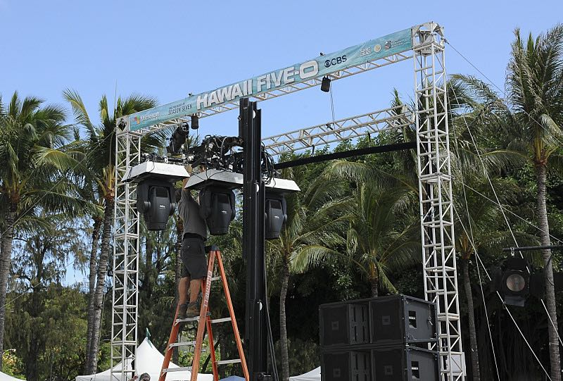 A stage hand works to finish setting up for the seventh annual Sunset on the Beach event, where thousands of Oahu residents and visitors gathered in Waikiki to watch the season seven premiere of Hawaii Five-0, titled Makaukau 'oe e pa 'ani, on Friday, Sept. 23, 2016, in Honolulu. Photo: Norman Shapiro/CBS © 2016 CBS Broadcasting, Inc. All Rights Reserved