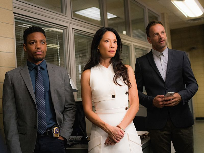 """""""Henny Penny the Sky is Falling"""" -- Captain Gregson lobbies to include Holmes and Watson when his unit is selected to receive a city commendation for its exemplary work. Also, as Holmes and Watson consult on the investigation into a financial analyst's murder, they are drawn into the world of asteroid research, on the 100th episode of ELEMENTARY, Sunday, Oct. 30 (10:00-11:00 PM, ET/PT) on the CBS Television Network. Pictured (L-R) Jon Michael Hill as Detective Marcus Bell, Lucy Liu as Joan Watson and Jonny Lee Miller as Sherlock Holmes Photo: Michael Parmelee/CBS ©2016 CBS Broadcasting, Inc. All Rights Reserved"""