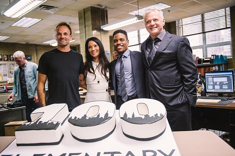 """Henny Penny The Sky Is Falling"" -- The cast of ELEMENTARY celebrates their milestone 100th episode with a cake-cutting ceremony Pictured (L-R) Picture (L-R) Jonny Lee Miller, Lucy Liu, Jon Michael Hill and Aidan Quinn Photo: Michele Crowe /CBS ©2016 CBS Broadcasting Inc. All Rights Reserved."