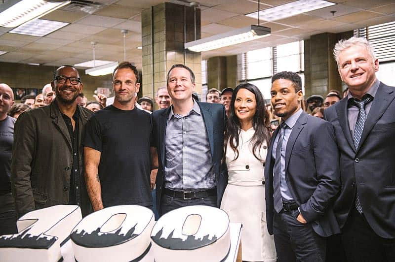 """Henny Penny The Sky Is Falling"" -- The cast of ELEMENTARY celebrates their milestone 100th episode with a cake-cutting ceremony Pictured (L-R) Executive Producer Carl Beverly, Jonny Lee Miller, Executive Producer Rob Doherty, Lucy Liu, Jon Michael Hill and Aidan Quinn Photo: Michele Crowe /CBS ©2016 CBS Broadcasting Inc. All Rights Reserved."