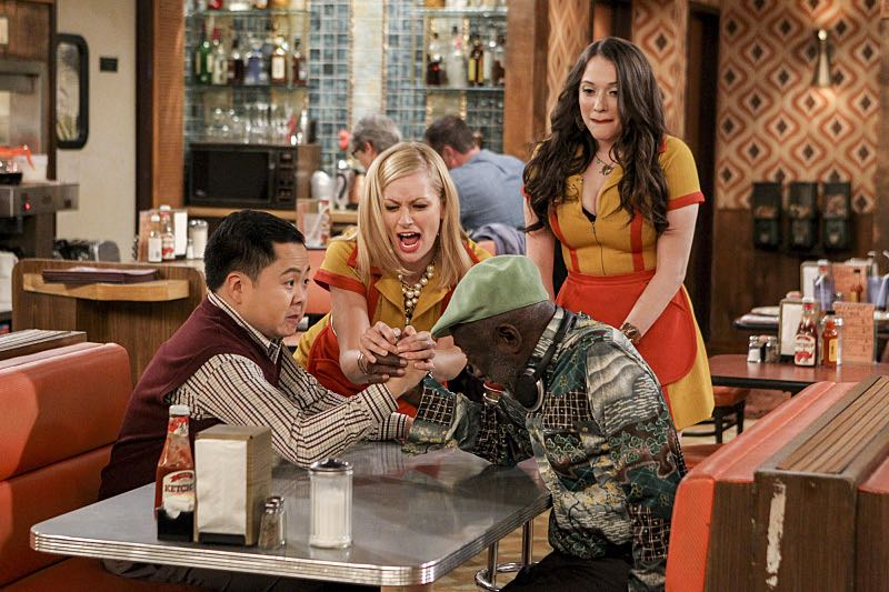 """And the 80's Movie"" -- Pictured: Han Lee (Matthew Moy), Caroline Channing (Beth Behrs), Max Black (Kat Dennings) and Earl (Garrett Morris). Max and Caroline's plans to attract a more sophisticated clientele to their dessert bar take a turn when Max befriends a bouncer whose team of arm wrestlers becomes their latest patrons. Also, Max and Randy continue to text each other, but when she runs out of sexy messages to send him, Oleg offers to be her ghost writer, on 2 BROKE GIRLS, Monday, Oct. 17 (9:00-9:30 PM, ET/PT), on the CBS Television Network. Dot Marie Jones (""Glee"") guest stars as arm wrestler Big Reba. Photo: Sonja Flemming/CBS ©2016 CBS Broadcasting, Inc. All Rights Reserved."