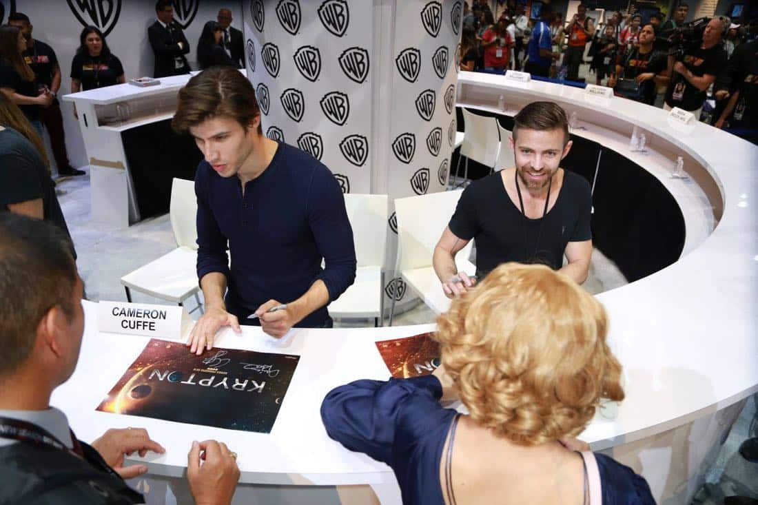 KRYPTON star Cameron Cuffe (left) and executive producer Cameron Welsh sign autographs for fans at the Warner Bros. booth at Comic-Con 2017 on Saturday, July 22. #WBSDCC (© 2017 WBEI. All Rights Reserved)