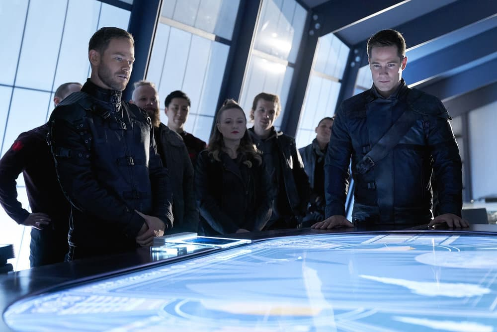 "KILLJOYS -- ""The Wolf You Feed"" Episode 307 -- Pictured: (l-r) Aaron Ashmore as John, Luke Macfarlane as D'Avin -- (Photo by: Steve Wilkie/Killjoys III Productions Limited/Syfy)"