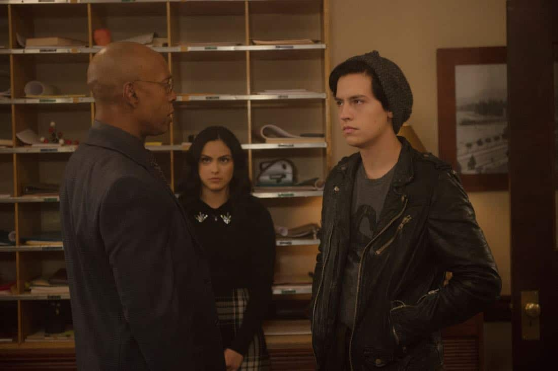 "Riverdale -- ""Chapter Twenty-Three: The Blackboard Jungle"" -- Image Number: RVD210a_0255.jpg -- Pictured (L-R): Peter Bryant as Principal Weatherbee, Camila Mendes as Veronica and Cole Spouse as Jughead -- Photo: Diyah Pera/The CW -- © 2018 The CW Network, LLC. All rights reserved."