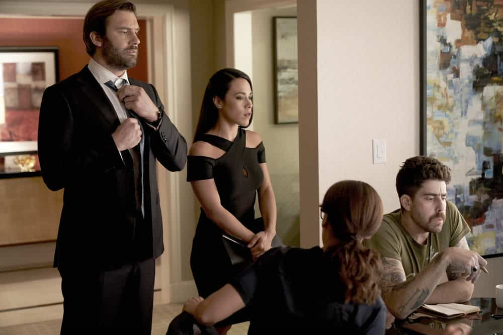 "TAKEN -- ""Charm School"" Episode 206 -- Pictured: (l-r) Clive Standen as Bryan Mills, Jessica Camacho as Santana, Adam Goldberg as Kilroy -- (Photo by: Steve Wilkie/NBC)"