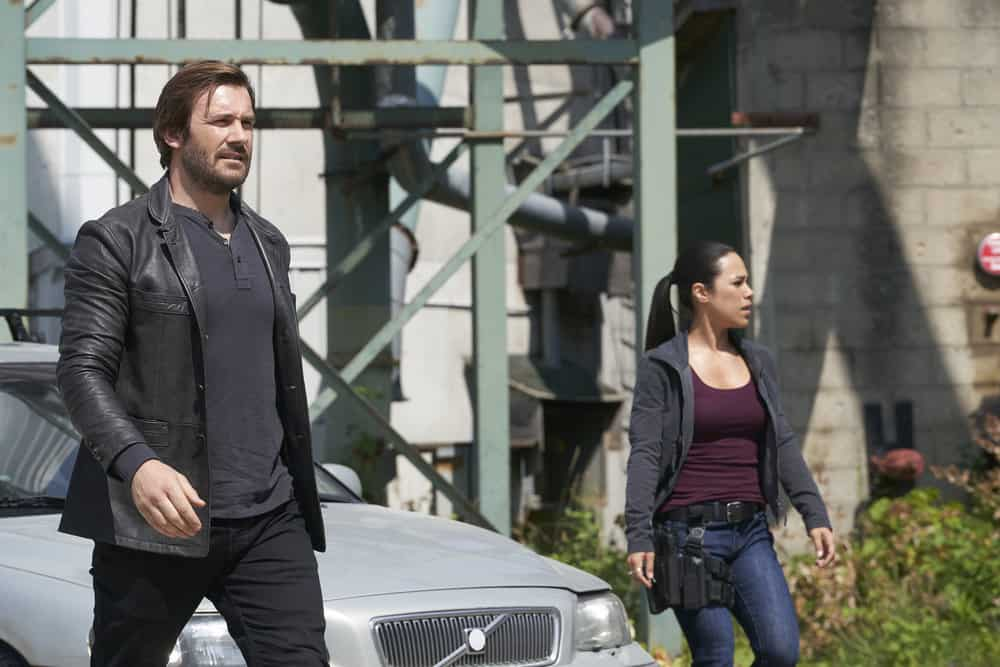 "TAKEN -- ""Charm School"" Episode 206 -- Pictured: (l-r) Clive Standen as Bryan Mills, Jessica Camacho as Santana -- (Photo by: Steve Wilkie/NBC)"