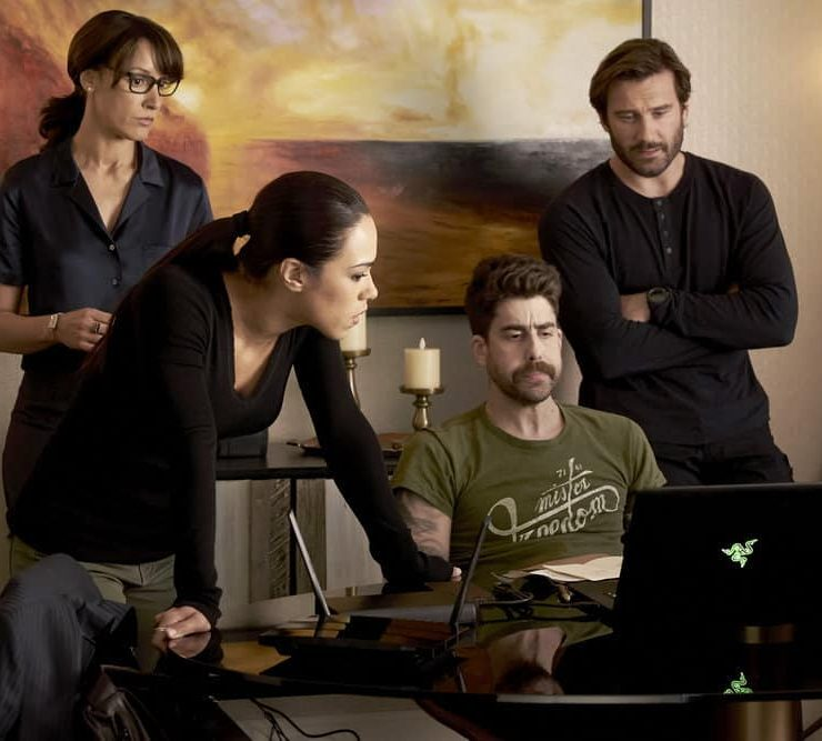 "TAKEN -- ""Charm School"" Episode 206 -- Pictured: (l-r) Jennifer Beals as Christina Hart, Jessica Camacho as Santana, Adam Goldberg as Kilroy, Clive Standen as Bryan Mills -- (Photo by: Steve Wilkie/NBC)"
