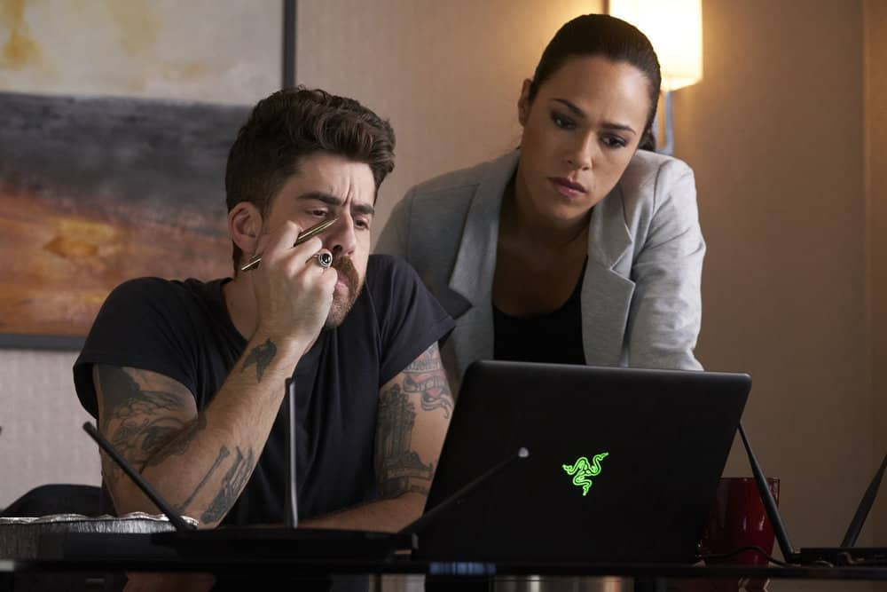 "TAKEN -- ""Charm School"" Episode 206 -- Pictured: (l-r) Adam Goldberg as Kilroy, Jessica Camacho as Santana -- (Photo by: Steve Wilkie/NBC)"