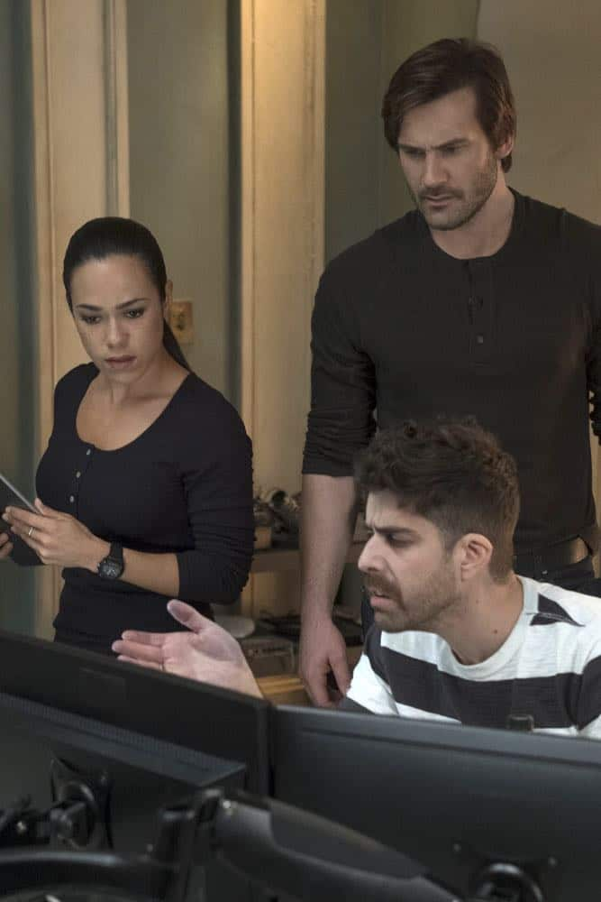 "TAKEN -- ""Strelochnik"" Episode 208 -- Pictured: (l-r) Jessica Camacho as Santana, Clive Standen as Bryan Mills, Adam Goldberg as Kilroy -- (Photo by: Panagiotis Pantazidis/NBC)"