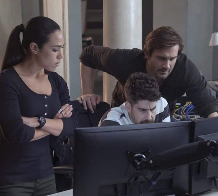 "TAKEN -- ""Strelochnik"" Episode 208 -- Pictured: (l-r) Jessica Camacho as Santana, Adam Goldberg as Kilroy, Clive Standen as Bryan Mills -- (Photo by: Panagiotis Pantazidis/NBC)"