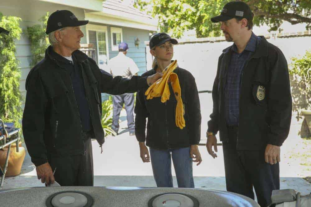 """Love Thy Neighbor"" -- After a Navy lieutenant is found murdered in his hot tub, the team interviews several families in the victim's peculiar neighborhood. Also, Torres must face the consequences after a volatile night out with Palmer, on NCIS, Tuesday, Oct. 2 (8:00-9:00 PM, ET/PT) on the CBS Television Network. Pictured: Mark Harmon, Emily Wickersham, Sean Murray. Photo: Michael Yarish/CBS ©2018 CBS Broadcasting, Inc. All Rights Reserved"