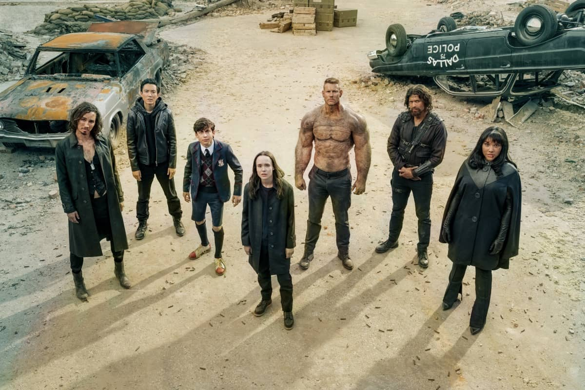 THE UMBRELLA ACADEMY (L to R) ROBERT SHEEHAN as KLAUS HARGREEVES, JUSTIN H. MIN as BEN HARGREEVES, AIDAN GALLAGHER as NUMBER FIVE, ELLEN PAGE as VANYA HARGREEVES, TOM HOPPER as LUTHER HARGREEVES, DAVID CASTAÑEDA as DIEGO HARGREEVES and EMMY RAVER-LAMPMAN as ALLISON HARGREEVES in episode 201 of THE UMBRELLA ACADEMY Cr. CHRISTOS KALOHORIDIS/NETFLIX © 2020
