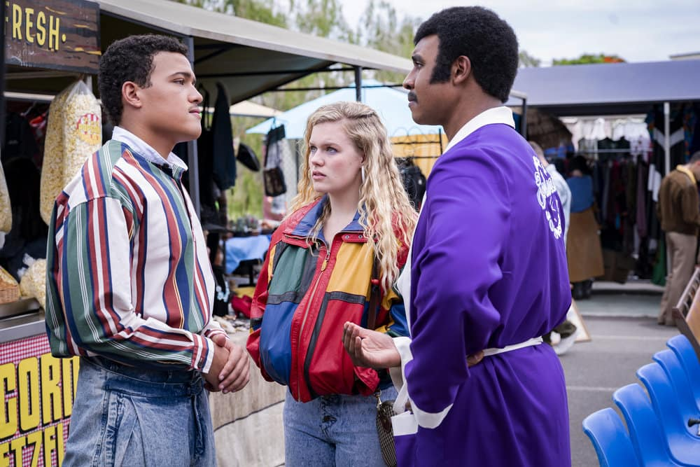 """YOUNG ROCK Season 1 Episode 2 -- """"On the Road Again"""" Episode 102 -- Pictured: (l-r) Bradley Constant as Dwayne, Lexie Duncan as Karen, Joseph Lee Anderson as Rocky Johnson -- (Photo by: Mark Taylor/NBC)"""