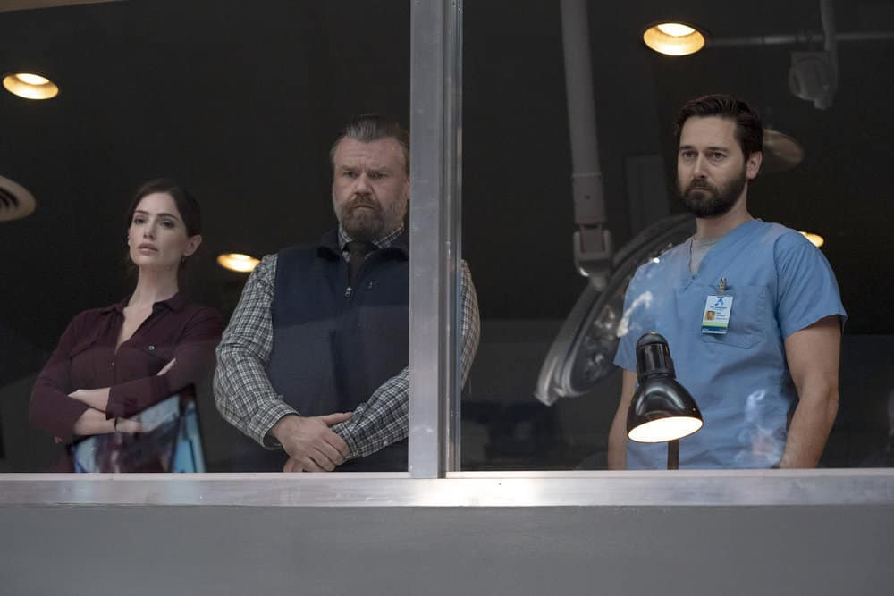"""NEW AMSTERDAM Season 3 Episode 2 -- """"Essential Workers"""" Episode 302 -- Pictured: (l-r) Janet Montgomery as Dr. Lauren Bloom, Tyler Labine as Dr. Iggy Frome, Ryan Eggold as Dr. Max Goodwin -- (Photo by: Virginia Sherwood/NBC)"""