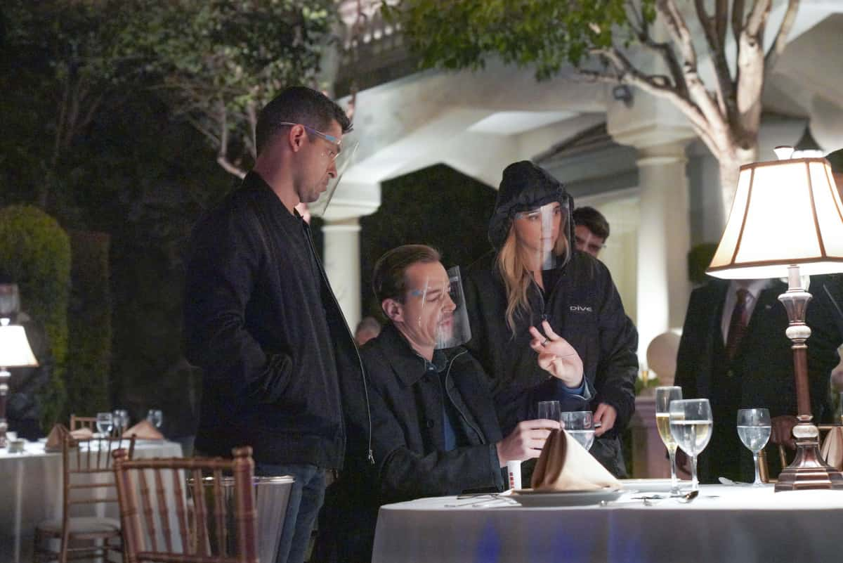 """NCIS Season 18 Episode 11 """"Gut Punch"""" – Vance assigns McGee, Torres and Bishop to COVID compliance duty at a foreign affairs summit, where they discover a link to another NCIS team's murder case, on NCIS, Tuesday, April 6 (8:00-9:00 PM, ET/PT) on the CBS Television Network. Rocky Carroll directed the episode. Pam Dawber guest stars as investigative journalist Marcie Warren. Pictured: Wilmer Valderrama as NCIS Special Agent Nicholas """"Nick"""" Torres, Sean Murray as NCIS Special Agent Timothy McGee, Emily Wickersham as NCIS Special Agent Eleanor """"Ellie"""" Bishop.  Photo: Bill Inoshita/CBS ©2021 CBS Broadcasting, Inc. All Rights Reserved."""