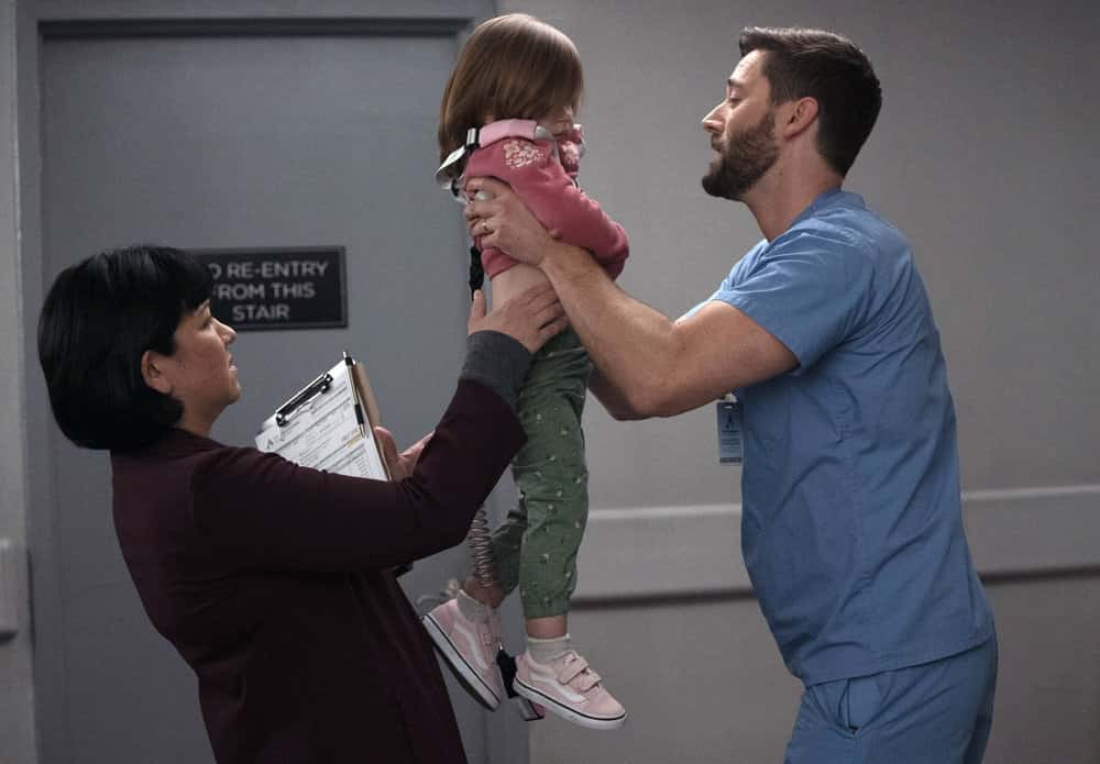 """NEW AMSTERDAM Season 3 Episode 7 -- """"The Legend of Howie Cournemeyer"""" Episode 307 -- Pictured: (l-r) Anna Suzuki as Sandra Fall, Nora and Opal Clow as Luna Goodwin, Ryan Eggold as Dr. Max Goodwin -- (Photo by: Virginia Sherwood/NBC)"""