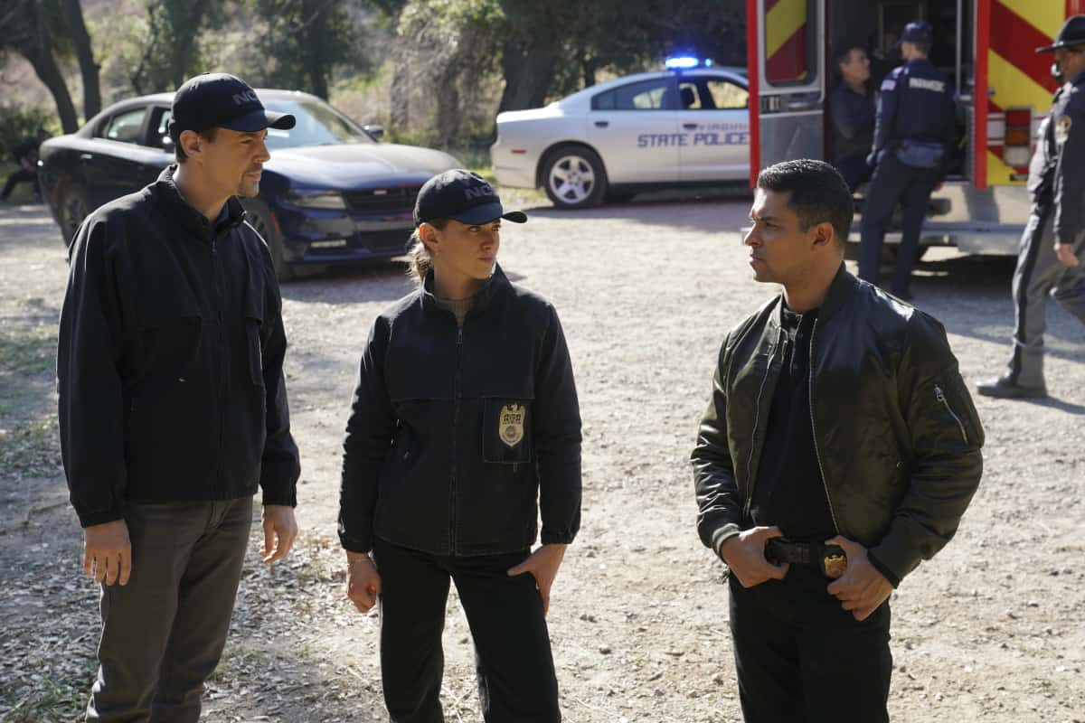 """NCIS Season 18 Episode 12 """"Sangre"""" – Evidence from the stabbing of a Marine Sergeant leads Torres to meet his father, Miguel (Steven Bauer), who left when he was a child, on NCIS, Tuesday, April 27 (8:00-9:00 PM, ET/PT) on the CBS Television Network. Pam Dawber returns as investigative reporter Marcie Warren. Pictured: Sean Murray as NCIS Special Agent Timothy McGee, Emily Wickersham as NCIS Special Agent Eleanor """"Ellie"""" Bishop, Wilmer Valderrama as NCIS Special Agent Nicholas """"Nick"""" Torres.  Photo: Sonja Flemming/CBS ©2021 CBS Broadcasting, Inc. All Rights Reserved."""