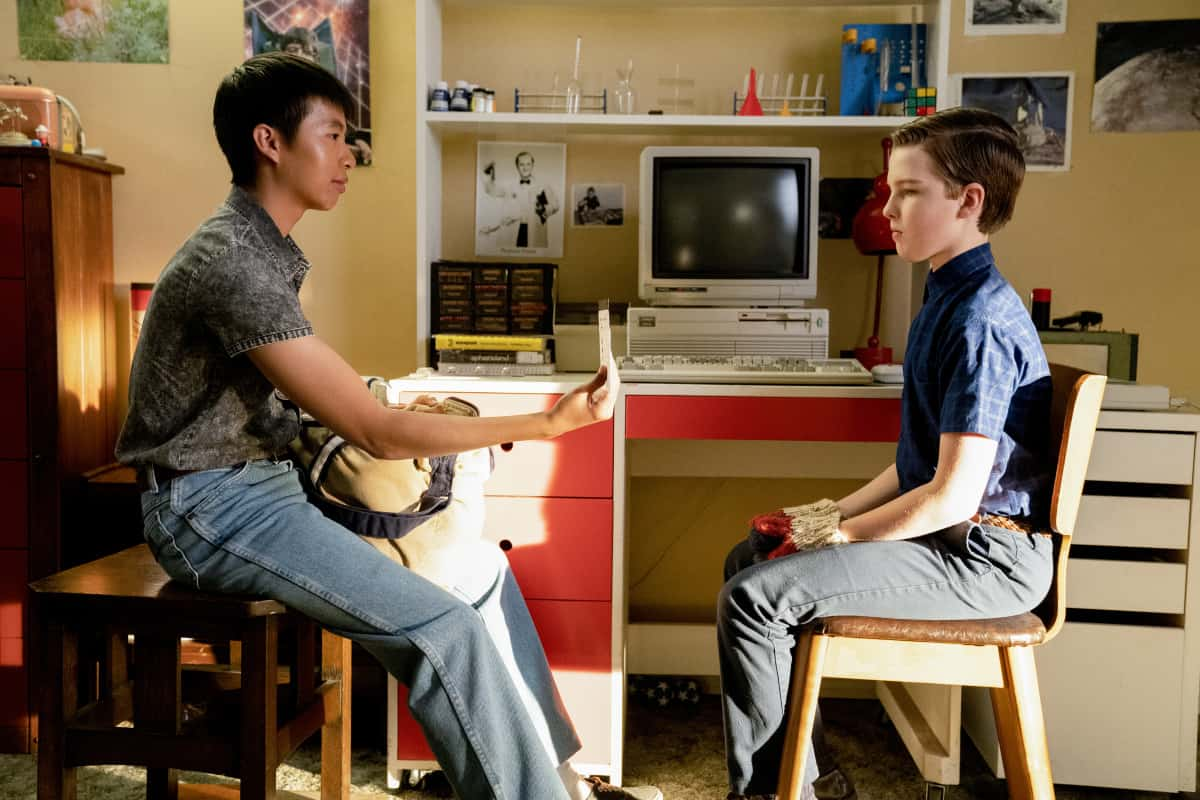 """Young Sheldon Season 4 Episode 15 """"A Virus, Heartbreak and a World of Possibilities"""" - Pictured: Tam (Ryan Phuong) and Sheldon (Iain Armitage). Sheldon is caught in a moral dilemma when offered a bootleg copy of a computer game he can't afford. Also, Mary and Meemaw take Brenda (Melissa Peterman) out for girls' night while George Sr. and the guys watch Billy, and Missy asks Georgie to take her and Marcus (London Cheshire) on a secret date, on YOUNG SHELDON, Thursday, April 22 (8:00-8:31 PM, ET/PT) on the CBS Television Network. Photo: Erik Voake/CBS ©2021 CBS Broadcasting, Inc. All Rights Reserved."""
