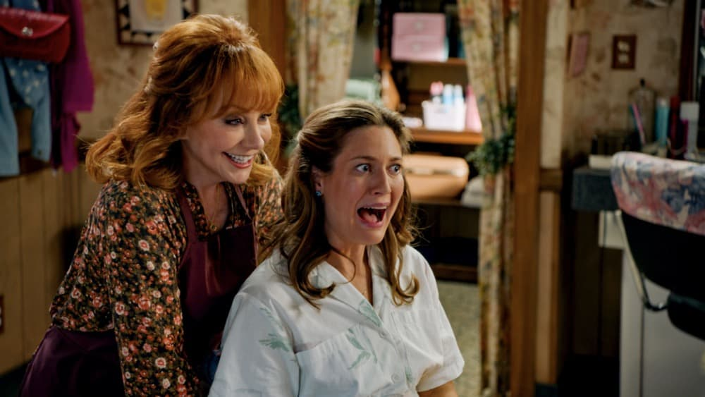 """Young Sheldon Season 4 Episode 16 """"A Second Prodigy and the Hottest Tips for Pouty Lips"""" - Pictured: June (Reba McEntire) and Mary (Zoe Perry). Sheldon finds himself at odds with Paige (Mckenna Grace) once again when she considers enrolling at East Texas Tech. Also, Mary seeks June's (Reba McEntire) advice when looking for a change, on YOUNG SHELDON, Thursday, April 29 (8:00-8:31 PM, ET/PT) on the CBS Television Network. Melissa Joan Hart returns to direct.  Photo Credit: Screen Grab/©2021 Warner Bros. Entertainment Inc. All Rights Reserved."""