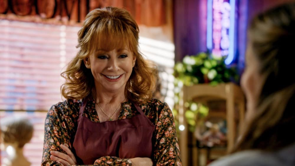 """Young Sheldon Season 4 Episode 16 """"A Second Prodigy and the Hottest Tips for Pouty Lips"""" - Pictured: June (Reba McEntire). Sheldon finds himself at odds with Paige (Mckenna Grace) once again when she considers enrolling at East Texas Tech. Also, Mary seeks June's (Reba McEntire) advice when looking for a change, on YOUNG SHELDON, Thursday, April 29 (8:00-8:31 PM, ET/PT) on the CBS Television Network. Melissa Joan Hart returns to direct.  Photo Credit: Screen Grab/©2021 Warner Bros. Entertainment Inc. All Rights Reserved."""