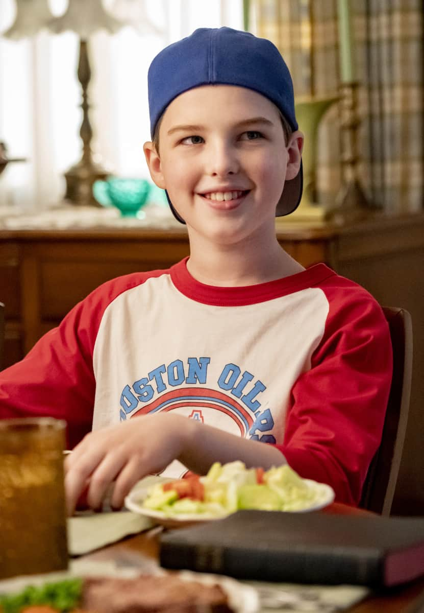 """YOUNG SHELDON Season 4 Episode 17 """"A Black Hole"""" - Pictured: Sheldon (Iain Armitage) in a baseball cap. The Coopers discuss the possibilities of black holes and alternate universes when Dr. Sturgis comes over for dinner, on YOUNG SHELDON, Thursday, May 6 (8:00-8:31 PM, ET/PT) on the CBS Television Network. Photo: Bill Inoshita/CBS ©2021 CBS Broadcasting, Inc. All Rights Reserved."""