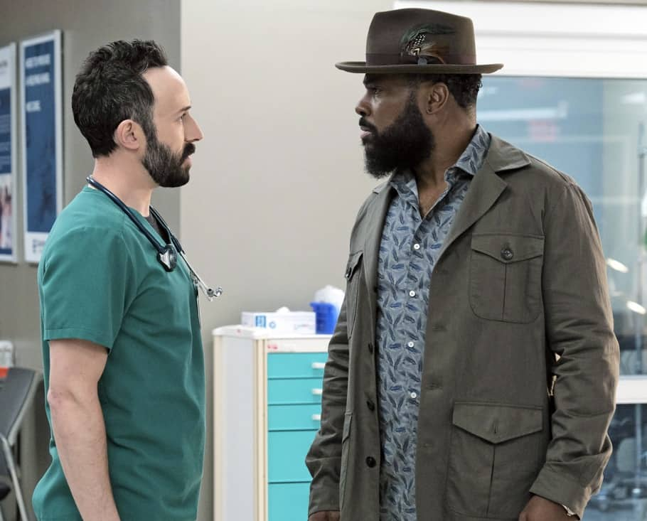 """THE RESIDENT Season 4 Episode 14 : L-R: Guest star Tasso Feldman and Malcolm-Jamal Warner in the season finale """"Past Present Future"""" episode of THE RESIDENT airing Tuesday, May 18 (8:00-9:01 PM ET/PT) on FOX. ©2021 Fox Media LLC Cr: Guy D'Alema/FOX"""