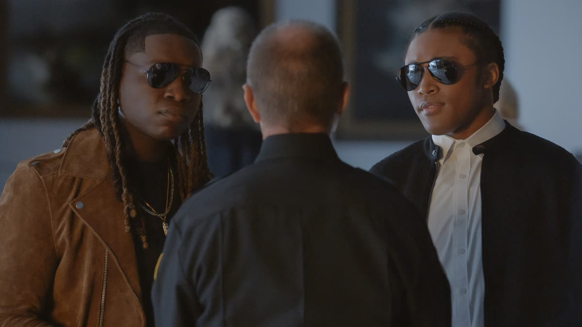 """LEGACIES Season 3 Episode 16 -- """"Fate's a Bitch, Isn't It?"""" -- Image Number: LGC316fg_0020r -- Pictured (L-R): Chris Lee as Kaleb and Quincy Fouse as Milton """"MG"""" Greasley -- Photo: The CW -- © 2021 The CW Network, LLC. All Rights Reserved."""