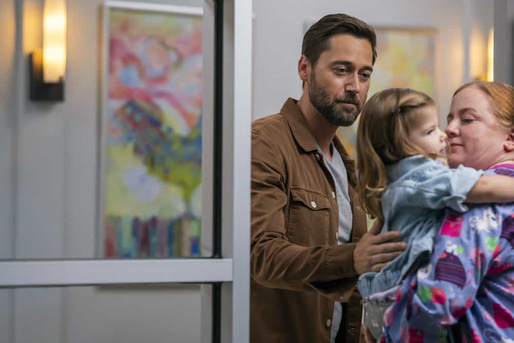 """NEW AMSTERDAM Season 4 Episode 1 -- """"More Joy"""" Episode 401 -- Pictured: (l-r) Ryan Eggold as Dr. Max Goodwin, Nora and Opal Clow as Luna Goodwin -- (Photo by: Zach Dilgard/NBC)"""