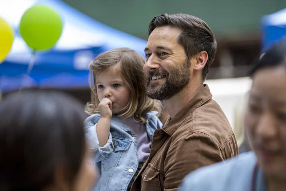 """NEW AMSTERDAM Season 4 Episode 1 -- """"More Joy"""" Episode 401 -- Pictured: (l-r) Nora and Opal Clow as Luna Goodwin, Ryan Eggold as Dr. Max Goodwin -- (Photo by: Zach Dilgard/NBC)"""